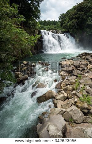 Splashing Waterfall Falling From Bedrock Between A Green Forests In Back Of River Flowing