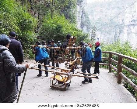 Chongqing , China - December 8, 2019 : Staff Carry Chairs To Service Tourists Walking Around Three N