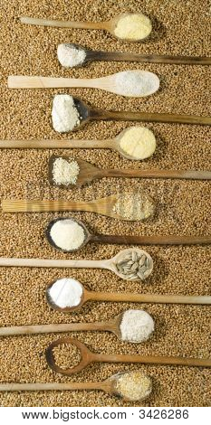Various Types Of Flour In Wooden Spoons On Wheat Background
