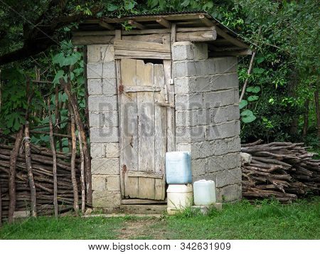 Rustic Wc. Rustic Outdoor Toilet Stands In The Garden. Rural Lifestyle, Latrine, Wc, Outhouse, Archi
