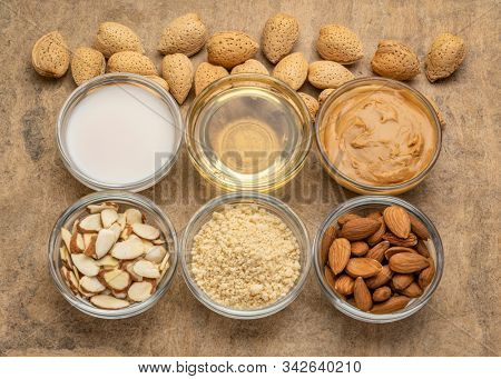collection of almond super foods: nuts, flour, slices, milk, oils and butter - top view of small glass bowls over textured bark paper
