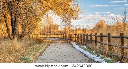 late fall scenery on a bike trail with cottonwood trees - panorama of Poudre River Trail in northern Colorado