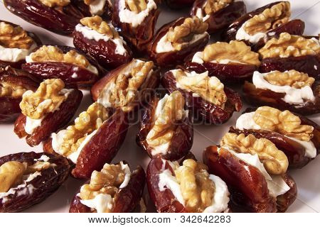 Close-up Of Fresh Dates Filled With Mascarpone Cheese And Walnuts In A White Dish.