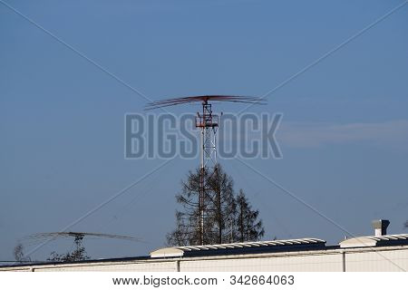 Antenna At The Airport, Radar System Near The Airport, Against A Blue Clear Sky With A Small Cloud.