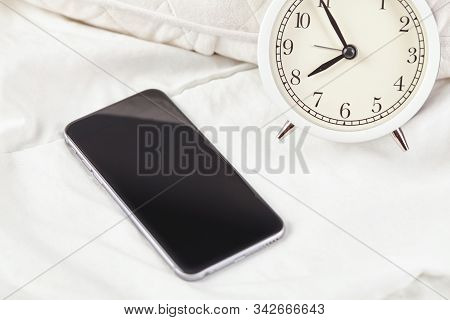 Smartphone And Alarmclock In Bed Room With Lighting Morning. Close Up.