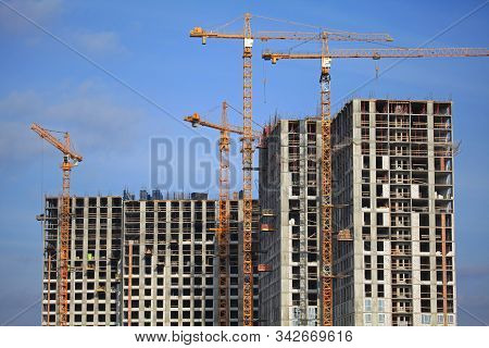 High-rise Construction Cranes And Array Of Buildings Under Construction On The Blue Sky Background.