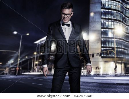 Elegant young handsome man over night city background poster