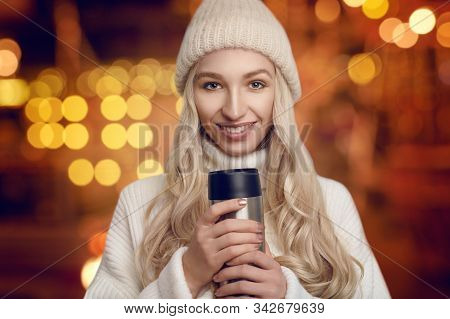 Pretty Young Woman In A Thick Woollen Sweater And Knitted Cap Cradling A Hot Beverage In Her Hands I
