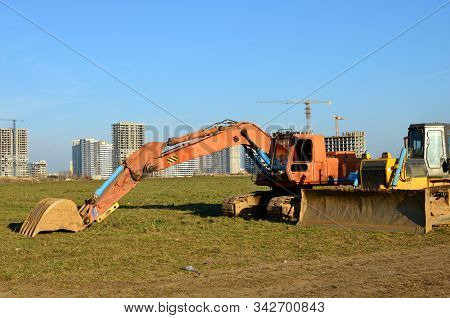 Crawler Excavator With Iron Bucket And Bulldozer At Construction Site. Land Clearing, Grading, Pool