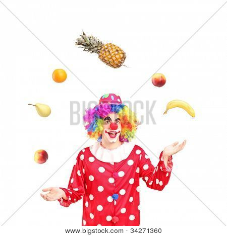A smiling clown juggling fruits isolated against white background