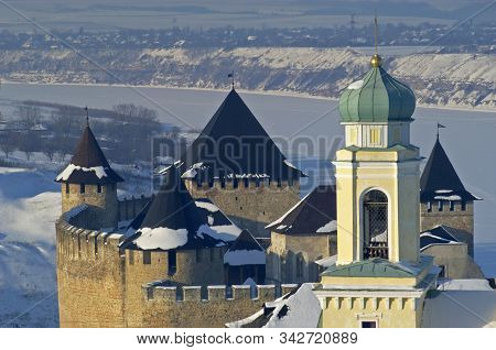 Khotyn Fortress And Yellow Church Against Winter Landscape