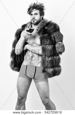 Fashion And Pathos. Richness And Luxury Concept. Guy Attractive Rich Posing Fur Coat On Naked Body.