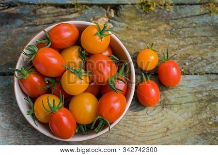 A fresh harvest of home grown miniature tomatoes in ceramic bowls.