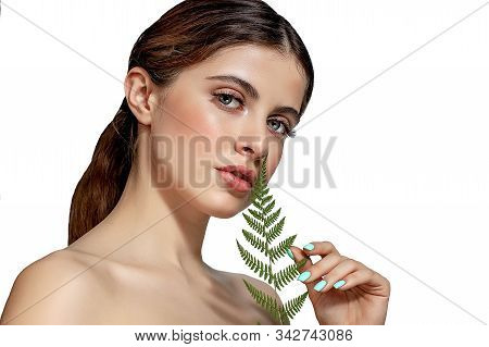 Portrait Of An Adult Brunette Woman On A White Background With Green Fern