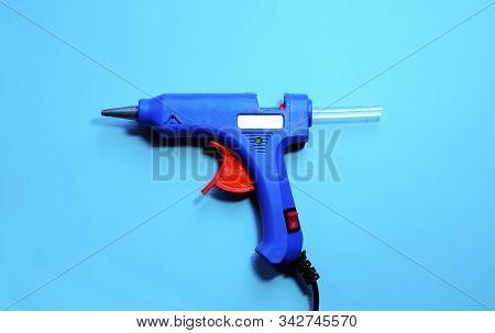 Electric Blue Hot Glue Gun With Glue Stick On A Blue Background