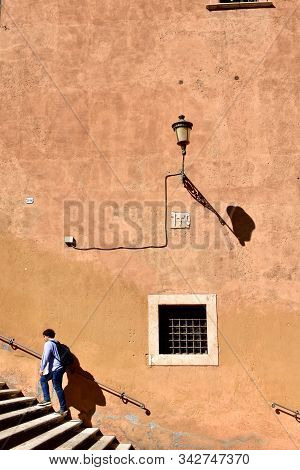 Rome, Italy. October 9, 2019. Ochre Wall, Streetlight And Stairs With Man Climbing At Capitoline Mus