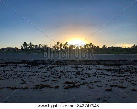 Large Orange Sun Behind Mansions In Florida
