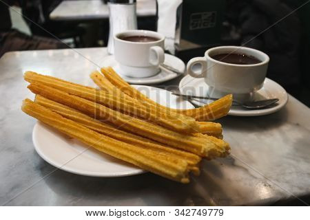 Churros And Mugs With Hot Chocolate At A Very Famous Spot In Madrid Called Chocolateria San Gines. 0