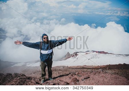 Male Tourist Stands With His Hands Up On The Top Of The Avachinsky Volcano On The Kamchatka Peninsul