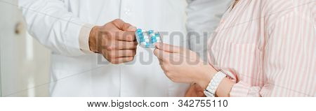 Cropped View Of Druggist Giving Blister With Pills To Female Customer, Panoramic Shot