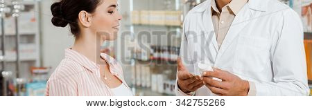 Side View Of Druggist Showing To Female Customer Jar Of Pills, Panoramic Shot