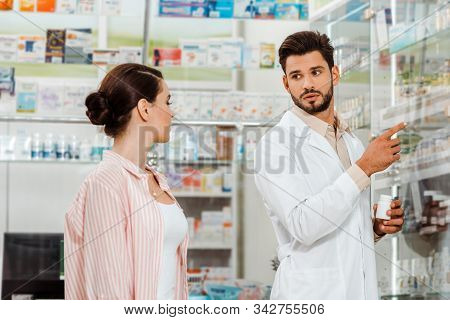 Druggist With Pills Pointing With Finger At Shelves With Medicaments To Customer
