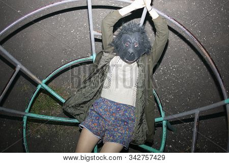 Funny Caucasian Girl Wearing Gorilla Mask, Coat And Shorts Lying On Metal Construction Of Children P