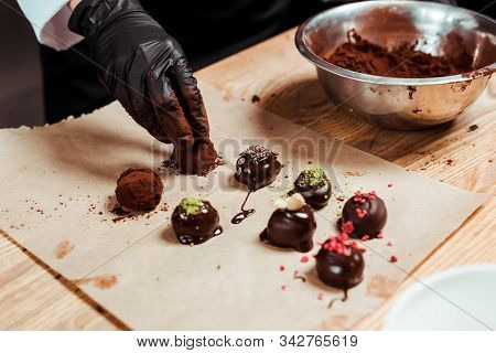 Cropped View Of Chocolatier In Black Latex Glove Preparing Truffle Candies Near Chocolate Balls