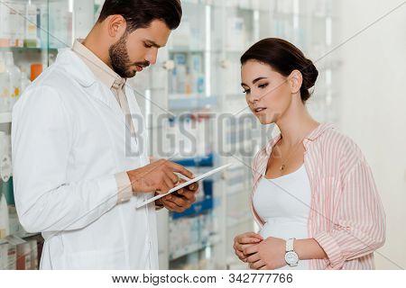 Druggist Using Digital Tablet Beside Pregnant Customer With Medicaments On Shelves At Background