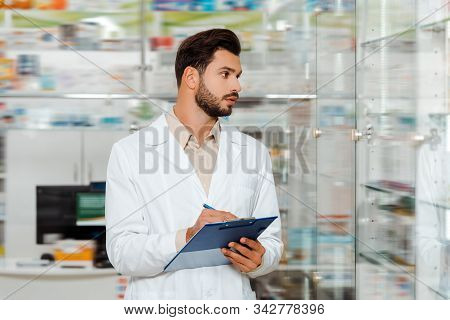 Selective Focus Of Druggist Writing On Clipboard By Drugstore Showcase