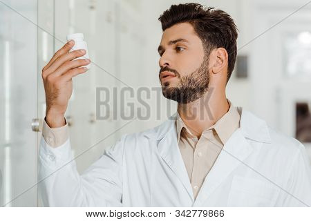 Druggist In White Coat Looking At Jar With Pills In Pharmacy