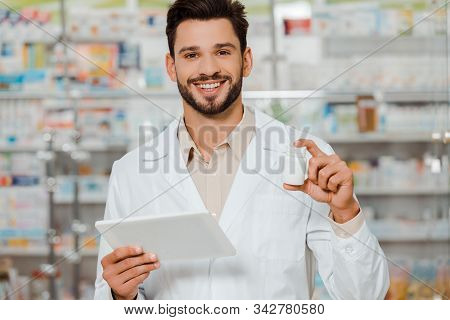 Pharmacist Smiling At Camera While Holding Pills And Digital Tablet In Apothecary