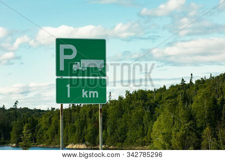 Trucks Parking Green Sign With A White Long Truck Symbol, After 1 Km, With Lake, Pine Trees, And Clo