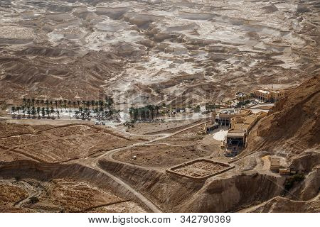 Masada Ancient Place As Touristic Attraction With Interesting Geological Surrounding And Palm Trees