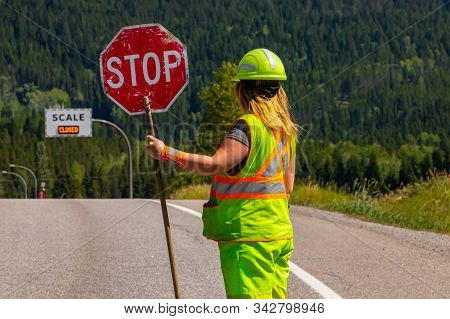 A Close Up And Rear View Of A Female Road Construction Worker Holding A Stop Stick Wearing High Visi