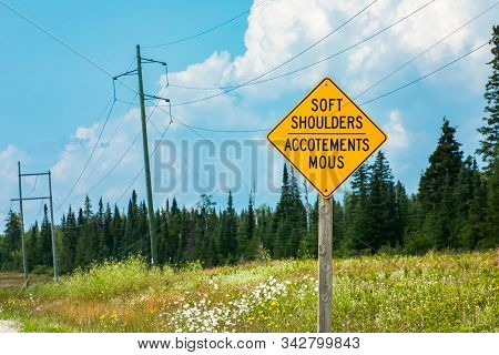 Soft Shoulders, Accotements Mous, Bilingual Road Warning Signs On Roadside, Selective Focus View Wit