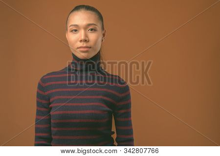 Young Beautiful Asian Transgender Woman Against Brown Background