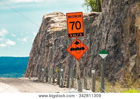 Temporary Condition Road Signs, An Orange Sign Shows The Maximum Safe Speed Is 70 Km With Bump Or Un