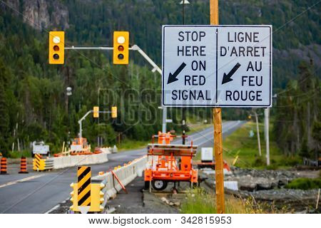 Selective Focus On A White Road Sign On Wooden Pole, Road Work Zone With Machines In The Background,