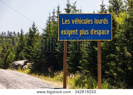 Blue Information Road Sign With French Yellow Writing, Heavy Vehicles Require More Space. On Rural C