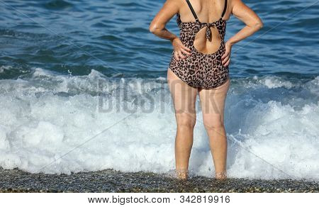 Fat Woman In Swimsuit On The Sea Beach .