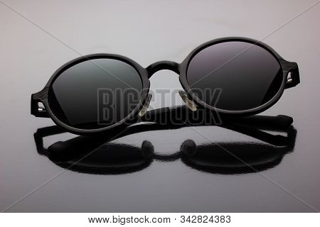 Black Polarized Sunglasses Round Shape On A Dark Background