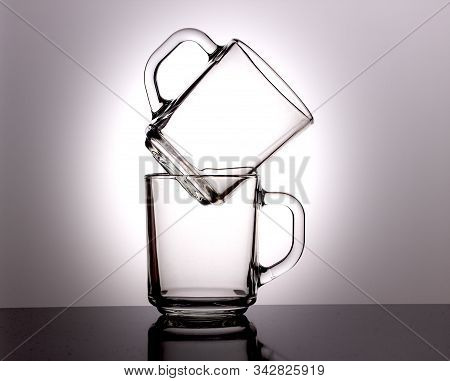 A Glass Transparent Tea Cup Stands On Another Cup Against A Dark Background