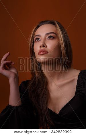 charming elegant fashion model wearing black dress with deep neckline posing on brown background. asian skinny young woman sits in sexy evening gown. beautiful sensual glamorous girl poses in studio poster
