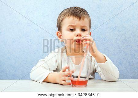 Cute Little Boy Drinking Juice On Light Blue Background. Lovely Kid Drink Grape Juice.