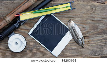 Fly fishing rod with  photo frame on wood background