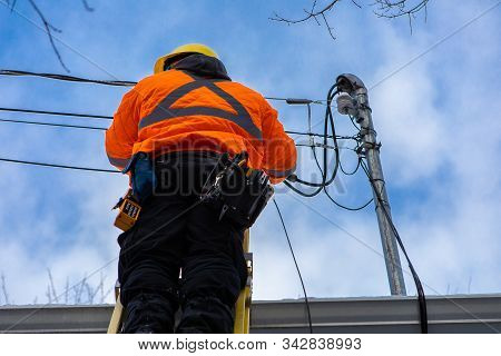 A Low Angle Shot Of A Domestic Service Provider Engineer Installing New Fiber Optic Cables To A Resi