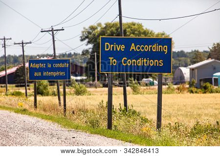 French, English Information Road Signs, Drive According To Conditions. On Canadian Rural Country Roa