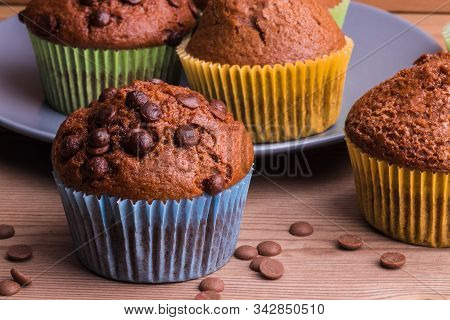 A Few Chocolate-sprinkled Muffins In Colored Cups On A Wooden Table. In The Background, Muffins On A