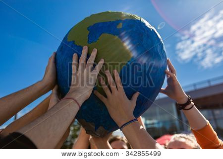 Close Up Of Group Of Hands Holding And Protecting Terra Globe With Lens Flares. Activist Expresion A